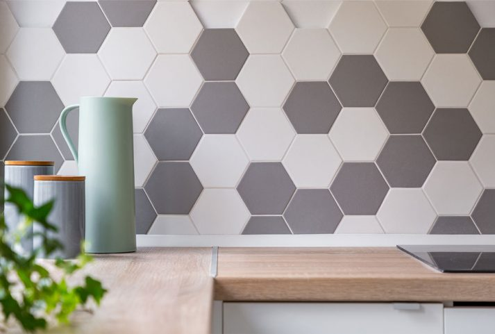 Kitchen with grey and white-honeycomb wall tiles an wooden worktop