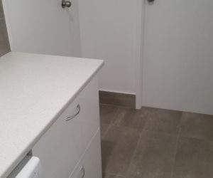 laundry area with drawer and doors